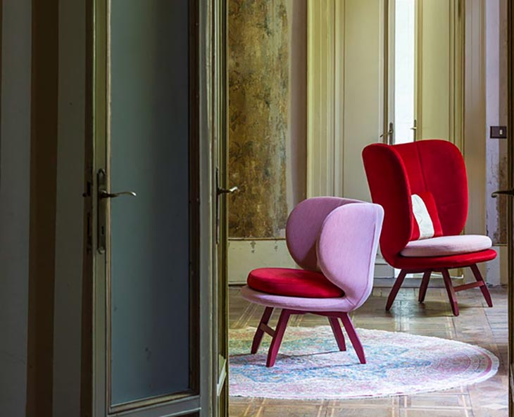 traditional room featuring modern moroso ayub chairs in red and lavender velvet