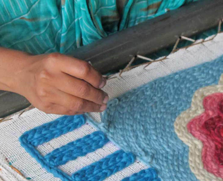 detail of person chain-stitching a gan embroidered rug