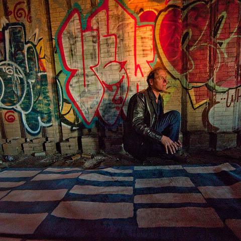 designer joseph carini against a graffitied brick wall