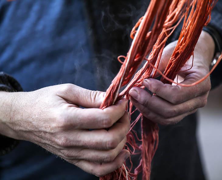 detail of rug maker inspecting orange yarn