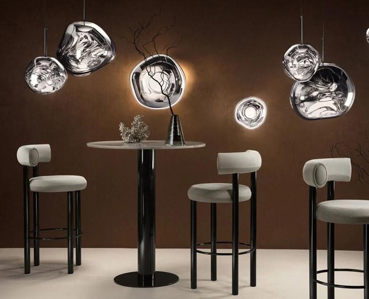 multiple melt pendant lights haning over fat stools by tom dixon