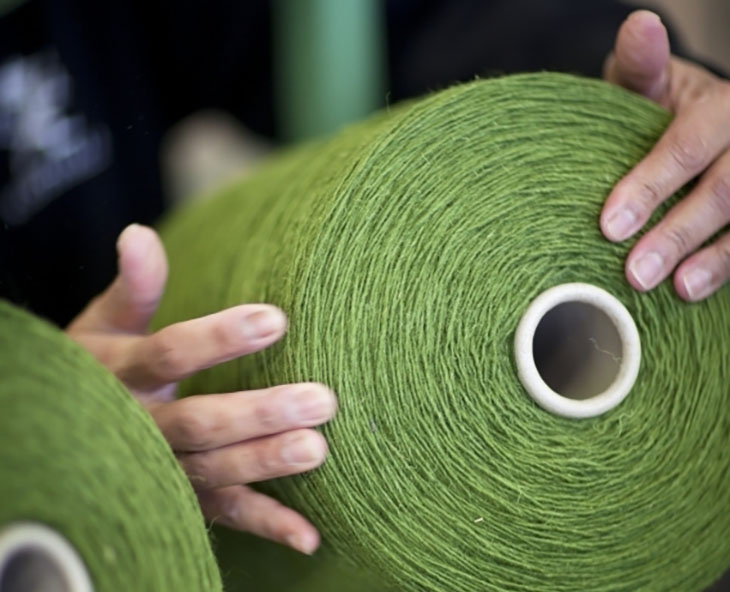 giant spools of green wool yarn at the kasthall rug factory