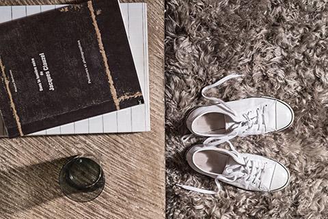 white tennis shoes on a beige yerra fur rug