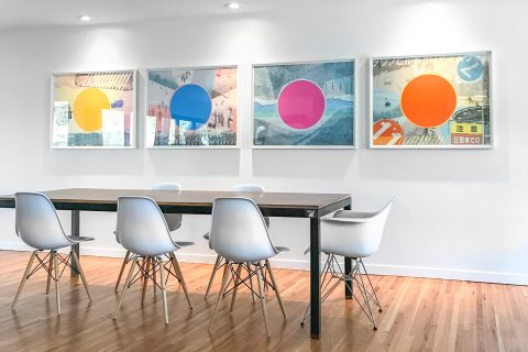 four artworks by jamie kripke hanging in a modern dining room
