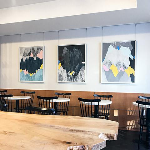 three artworks by jamie kripke hanging in a modern restaurant
