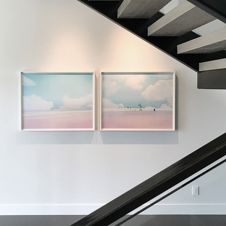 two artworks by jamie kripke hanging near a modern staircase