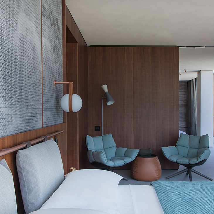modern bedroom featuring two b&b italia husk armchairs with wood base