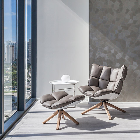 bright interior space featuring b&b italia husk armchair and ottoman with wood base