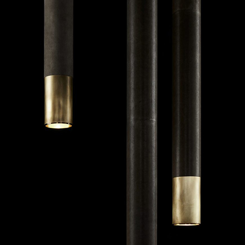 close up of three apparatus cylinder pendants in aged brass finish with leather wrap