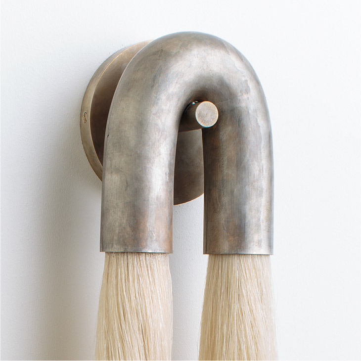 close up of an apparatus horsehair sconce with tarnished silver metal and flaxen hair