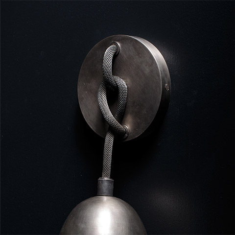 close up of an apparatus lariat sconce on a black background