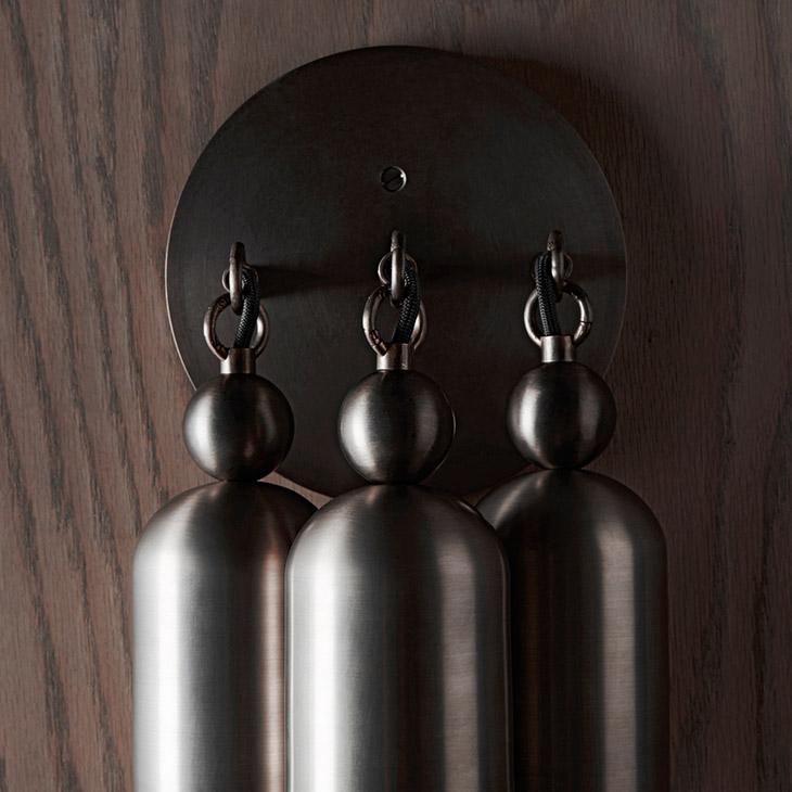 close up of apparatus tassel 3 sconce hardware