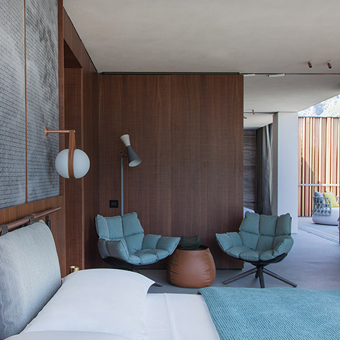 modern bedroom featuring a b&b italia lady fat ottoman