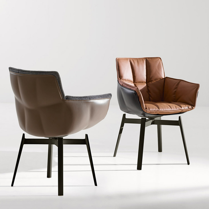 a pair of b&b italia husk chairs with metal base on a grey background