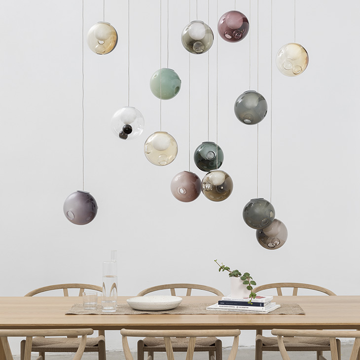 scandinavian style dining room featuring colorful bocci 28 series pendant light