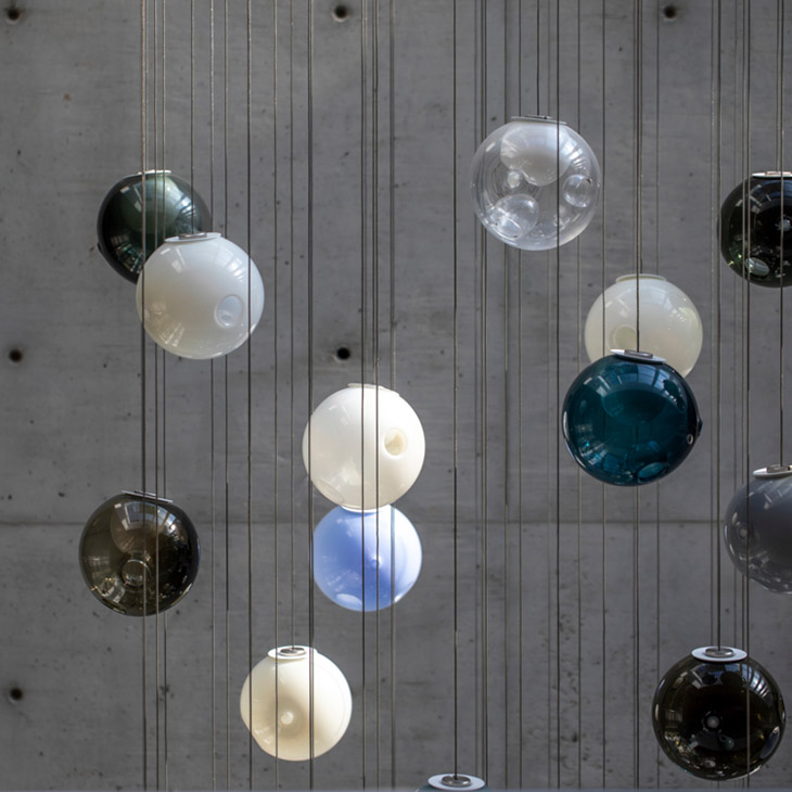 colorful bocci 28 series pendant lights hanging in front of concrete wall