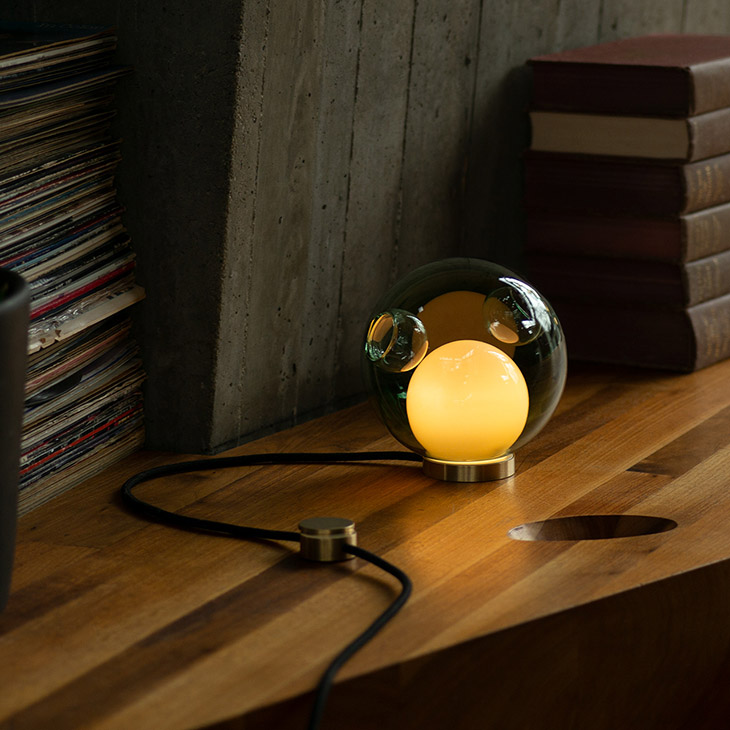 interior space featuring bocci 28t table lamp on wood shelf