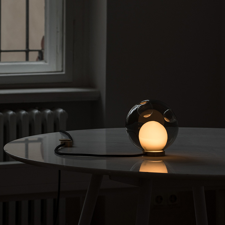 dark interior space featuring a glowing bocci 28t table lamp on a table