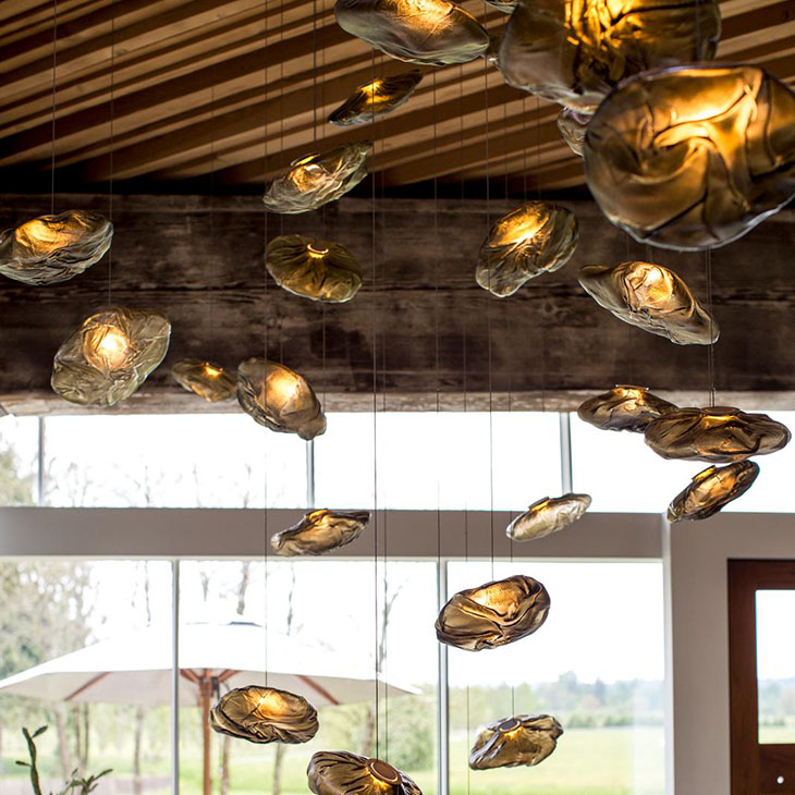 close up of bocci 73 pendant lights with an outdoor setting in the background