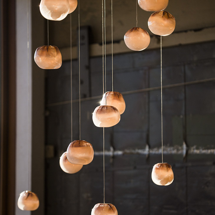 close up of bocci 84 series pendant light glowing in a warehouse space