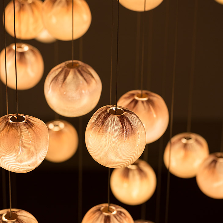 close up of bocci 84 series pendant light glowing in a dark room