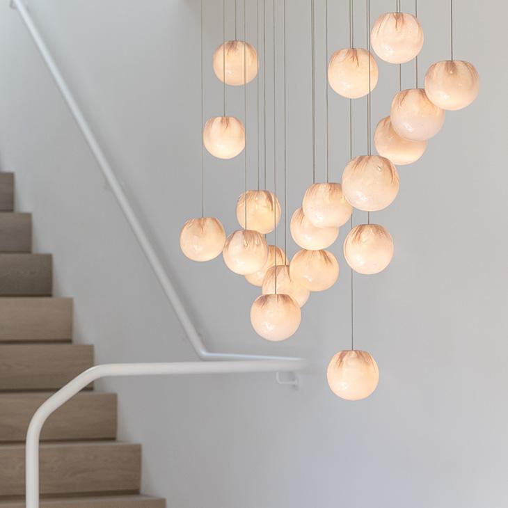 modern stairwell featuring bocci 84 series pendant light