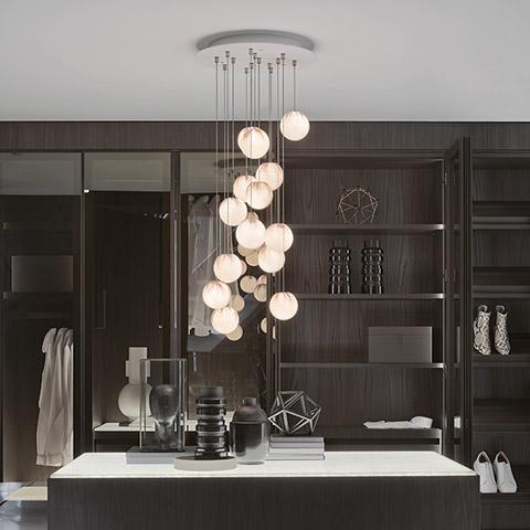 modern walk-in closet featuring bocci 84 pendant light