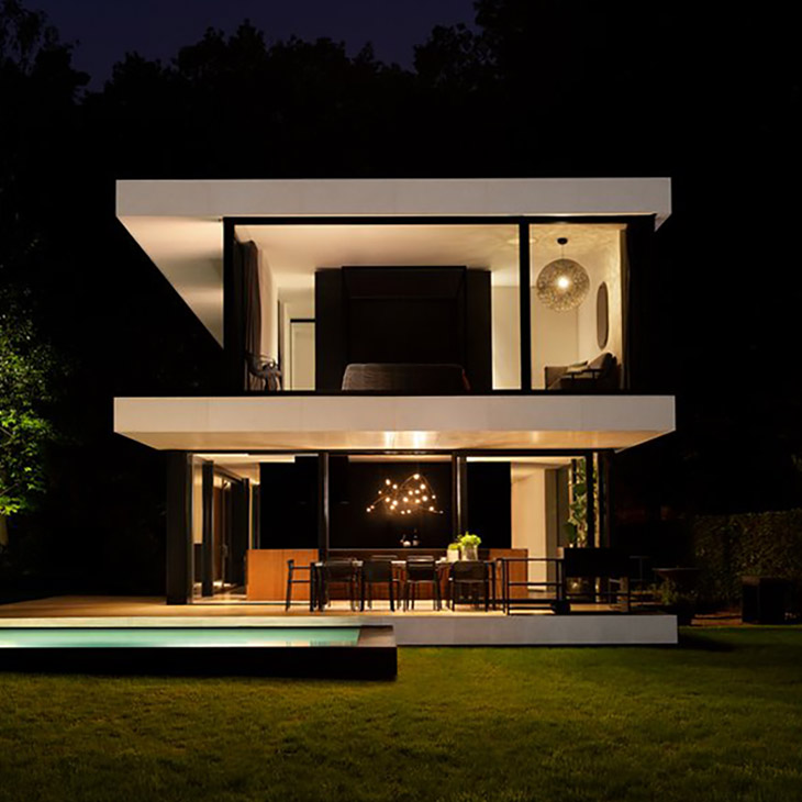 exterior of a modern house featuring a moooi flock of light pendant glowing in the first floor window