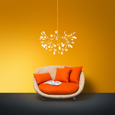 moooi heracleum II suspended pendant light hanging above an armchair