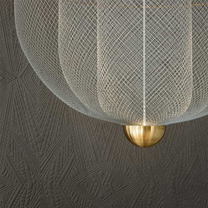 close up of a moooi meshamatics pendant light against a grey wallpapered wall