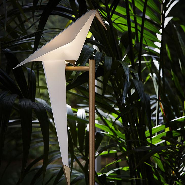 moooi perch light floor lamp nestled in palm trees