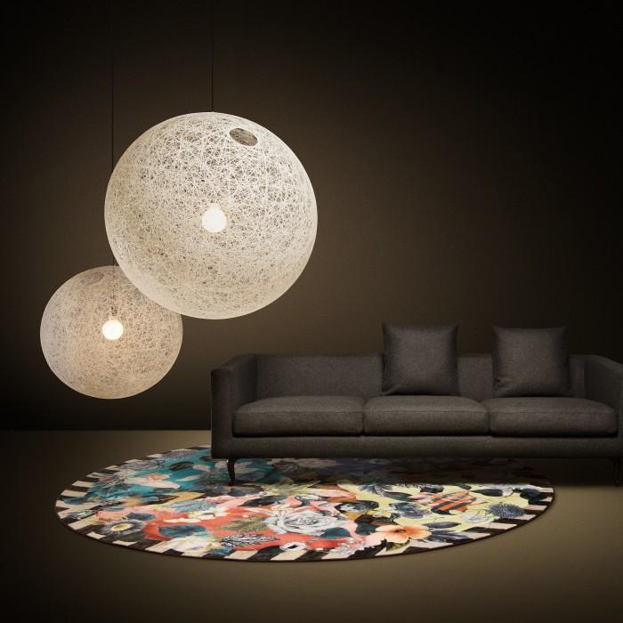 two white moooi random light II pendants hanging above a sofa
