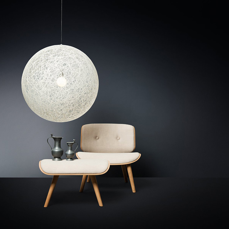 moooi random light II pendant in white hanging above a chair and ottoman
