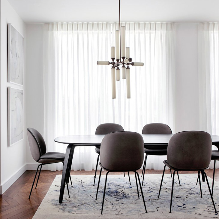 modern dining room featuring a roll & hill castle pendant