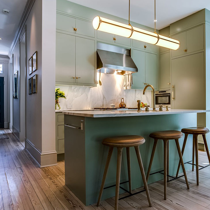 modern kitchen featuring a roll & hill endless pendant 3 units in brass