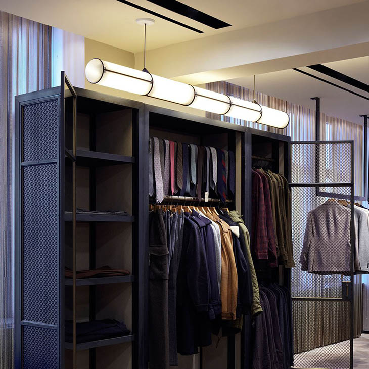 modern walk-in closet featuring a roll & hill endless pendant 5 units in black
