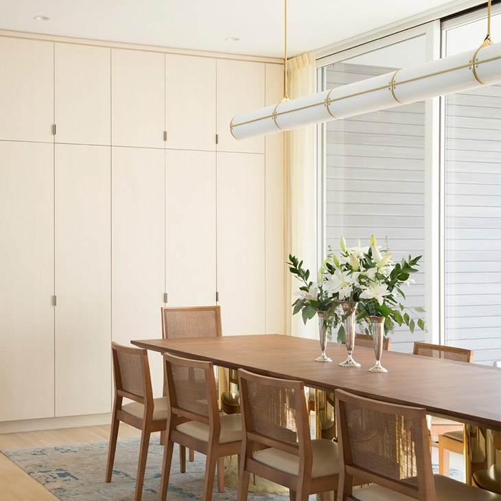 modern dining room featuring a roll & hill endless pendant 5 units in brass