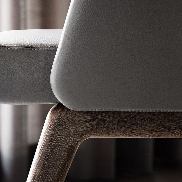 close up of leather upholstery and sucupira legs on a minotti reeves dining chairs